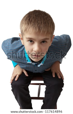 surprised boy sitting on a chair isolated on white