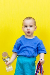 Surprised boy with sports awards on yellow background.