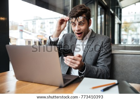 Surprised business man in eyeglasses sitting by the table in cafe while holding smartphone and looking at laptop computer