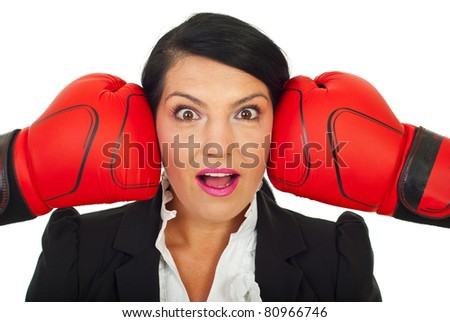 Surprised business woman face between two boxing gloves isolated on white background