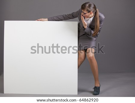 surprised business woman with blank board over grey background - stock photo