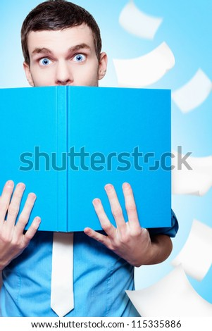 Surprised Businessman Peeping Over The Top Of A Business Planning Text Book In A Depiction Of A Market Research Idea