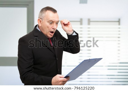 Surprised businessman reading a document in his office #796125220