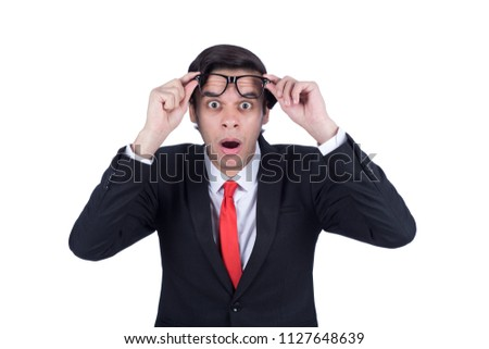 Surprised businessman wearing a suit raising the glasses he wears on the forehead shocked, isolated on a white background. #1127648639
