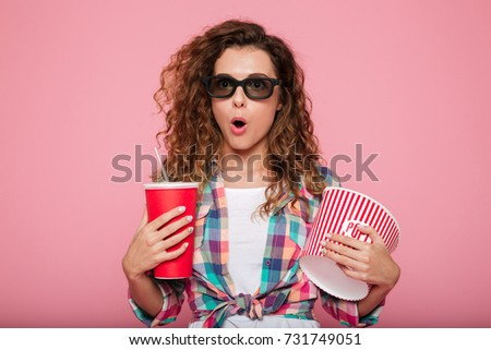Surprised caucasian woman in 3d glasses holding cola and popcorn and looking camera isolated over pink #731749051