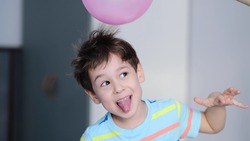 surprised cheerful boy with thorns in his hair without static electrification. Physics, electrical electrification balloon test. Positively and negatively charged atoms. School lesson experiment.