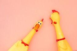 Surprised chicken toys are isolated on a pastel pink background, one looks at the camera and shouts, the other one to the side. Screaming chicken toys on a coral background. Copyspace