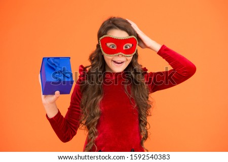Surprised child wear carnival mask. Little girl hold surprise box. Receiving festive surprise. Birthday surprise. Gift wrapping. Holiday preparation.