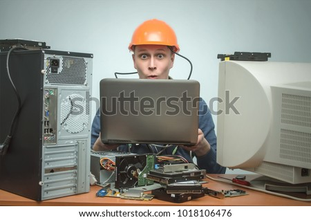 Surprised Computer technician work on laptop computer and is installing a new software. PC repair service center. #1018106476