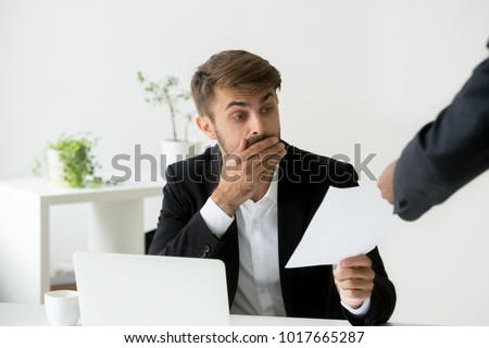 Surprised confused caucasian employee receiving dismissal notice, letter or document with unexpected news from african boss, worried shocked office worker getting fired in written message at work