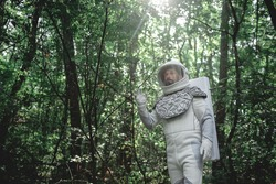 Surprised cosmonaut wearing white armor and helmet is standing among trees. He looking ahead with bewilderment in his eyes. Low angle. Copy space on left side