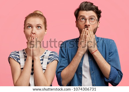 Surprised couple looks with shocking expression upwards, cover mouth, notice something amazing in sky. Beautiful blonde fashionable female and her best friend pose together with stunned looks