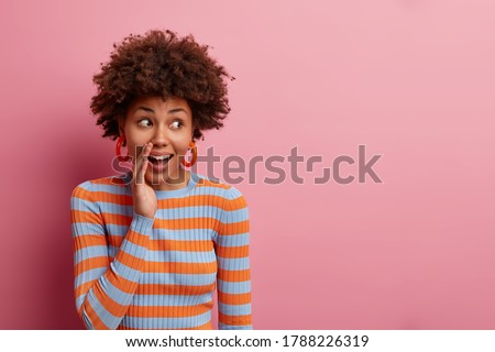 Surprised curious curly woman keeps hand near mouth and whispers secret, spreads rumors, looks with wondered expression aside, dressed casually, isolated on pink background, blank empty space