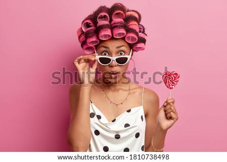 Surprised dark skinned woman wears sunglasses, hair rollers, holds sweet lollipop, makes hairstyle, pink background