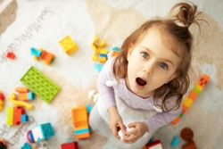 Surprised emotional little adorible child girl with big blue eyes siting on the floor in the children's room. Play with colored blocks. Lifestyle photo from above.