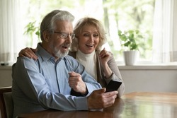 Surprised excited OAP family couple getting amazing good news from video call. Happy middle aged pensioners using mobile phone together at home, talking to relations, looking at screen and gasping