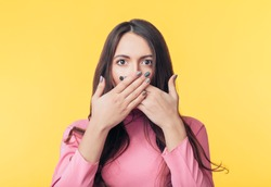 Surprised excited woman covering her mouth with hands isolated on yellow background