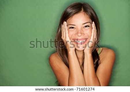 Surprised excited woman on green background. Cheerful multiracial ...