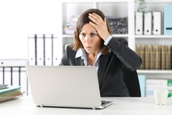 Surprised executive lady making mistake on laptop sitting on a desk at office