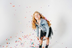 Surprised fashionably dressed curly hair tween girl in in a denim jacket and black tutu skirt and rough boots on white background with colorful confetti