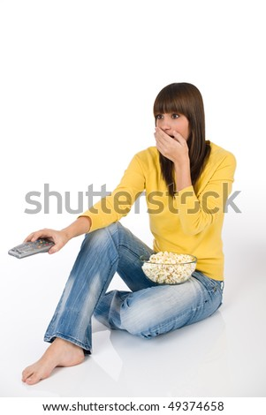 Surprised female teenager watching television holding remote control, eating popcorn