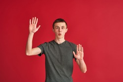 surprised, frightened young man stands in a mime pose with his arms outstretched on a red background, as if looking through a glass. The concept of a hopeless situation, problems, fear, claustrophobia