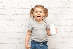 Surprised funny adorible child girl with pill on her tongue and holding white mockup bottle medicine. Pills and vitamins for kids. Vitamin and mineral complex. Medicine concept. Banner, place for text
