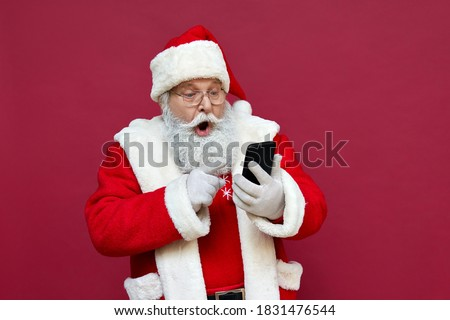 Photo of  Surprised funny amazed old bearded Santa Claus wearing costume holding cell phone using mobile app on smartphone shocked by Christmas promotion, xmas applications ads isolated on red background.