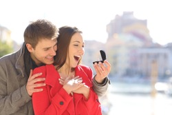 Surprised girl gets engagement ring from boyfriend on marriage proposal on a beach town in winter