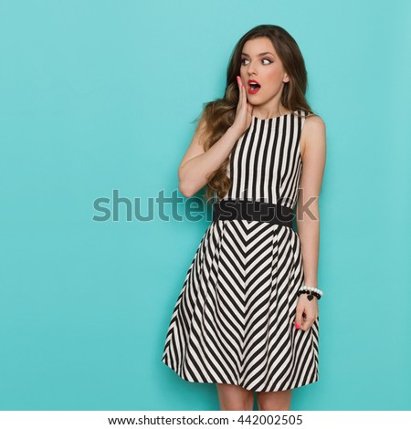 Surprised girl in black and white striped dress holding hand on chin and looking away, Three quarter length studio shot on turquoise background.