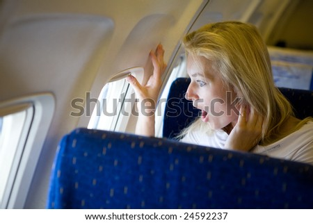 surprised girl in the airplane - stock photo