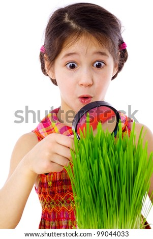 Surprised girl looking at the grass through a magnifying glass, isolated on white