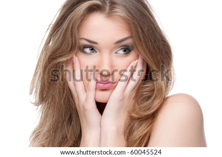 Surprised girl on a white background touches her face