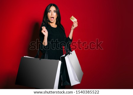 Surprised glamourous woman carrying shopping bags holding a gold credit card on dark red background.