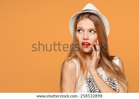Surprised happy beautiful woman looking sideways in excitement. Isolated over orange background