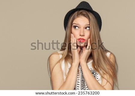 Surprised happy beautiful young woman looking up in excitement. Fashion girl in hat. isolated on beige background