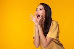 Surprised happy beauty asian woman looking copy space in excitement. Expressive facial expressions. Presenting some product. Beautiful girl act like a telling secret Isolated on yellow background