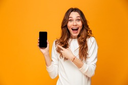 Surprised happy brunette woman in sweater showing blank smartphone screen and pointing on it while looking at the camera with open mouth over yellow background