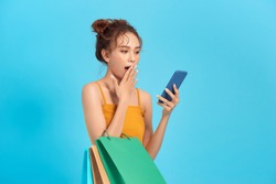 Surprised happy woman holds cheap paper shopping bags looks at phone