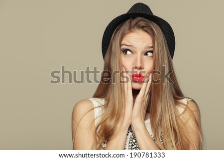 Surprised happy young woman looking up in excitement. Fashion girl in hat. isolated on beige background