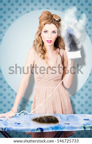 Surprised housewife holding iron with cooked ironing board. Burnt out on house cleaning chores - stock photo