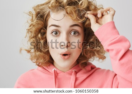 Surprised intrigued curly-haired feminine woman taking off glasses and saying wow while standing over gray background and glancing at camera. Girl did not recognized her friend who changed haircut