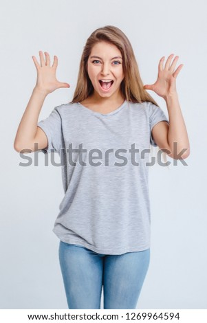 Surprised joyful girl on gray background in t-shirt looks with smile and holds hands with palm open at head. Concept of surprise solemnity surprise.Vertical. #1269964594