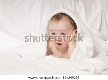 Surprised kid looks out from under a white blanket