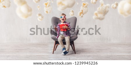 Surprised kid with popcorn in 3d glasses in the cinema