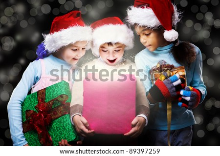 Surprised kids in Santa hats looking inside the present box