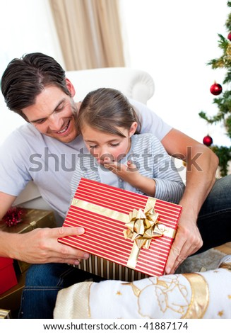 Surprised little daughter opening a Christmas present with her father at home