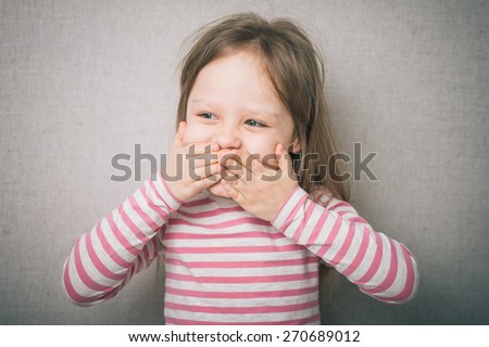 surprised little girl covered his mouth with his hands