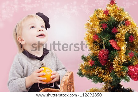 Surprised little girl looking up under Christmas tree