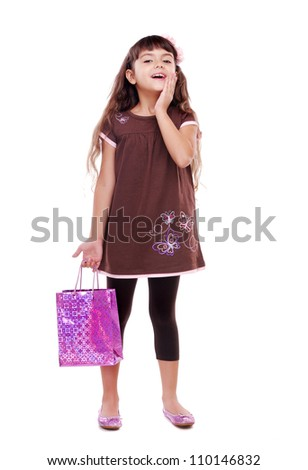 Surprised little girl with paper shopping bag